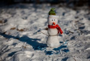 Miniature Christmas snowman in a knitted dress with ornaments